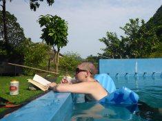Maeve living her best life: book, beer, pool.