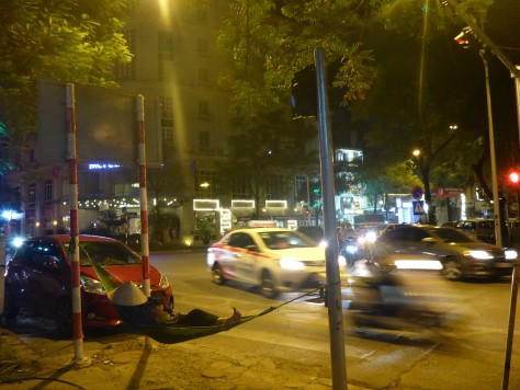 A guy casually napping in a hammock on a main road next to HaNoi train station